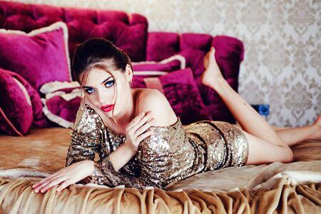 Une femme sexy est allongée sur le lit. Jeune mannequin de beauté avec un maquillage parfait. Photo de mode. Banque d'images
