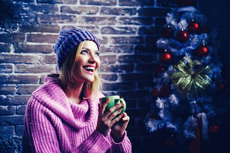 Mulled wine, winter drinks. Portrait of a young beautiful smiling, winter woman. Happy new year. Christmas tree decorate at home. Smiling woman decorating Christmas tree at home.