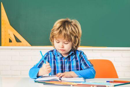 Child near chalkboard in school classroom. Happy school kids at lesson. Cute Preschool in Classroom.