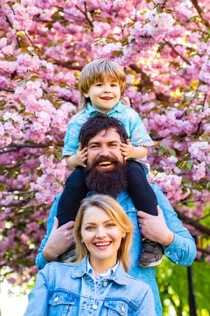 Parents giving piggyback ride to child. Happy family outdoors. Mother father and son. Portrait of family fun outside. Mother father and son. Happy family outdoors. Stock Photo