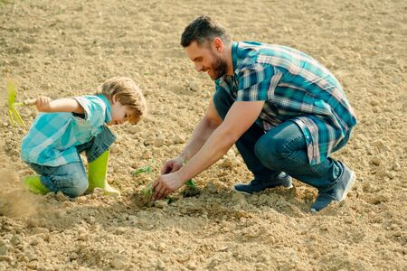 Father and son work on earth ground. Family planting. Daddy teaching little boy to do gardening.