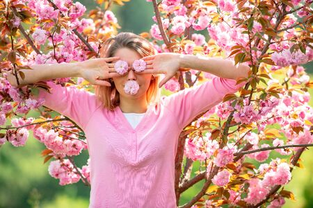 Funny girls with blooming sakura cherry Flover. Closing eyes with flovers. Hides eyes. 8 march womens day.