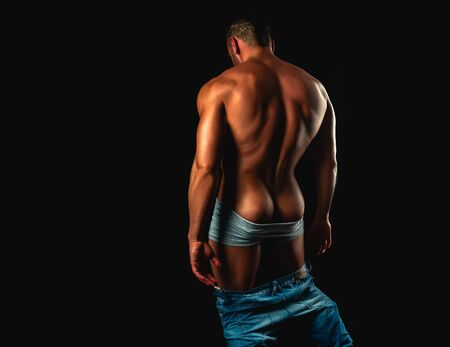 Hombre musculoso. Retrato de moda sexy de chico joven caliente. Glúteos masculinos. Espalda fuerte. Maromo masculino con cuerpo atlético.