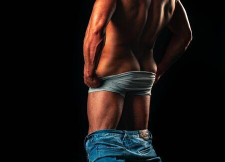 Chico. Hombre musculoso, hombre atlético fuerte mostrando su espalda perfecta aislada sobre fondo negro