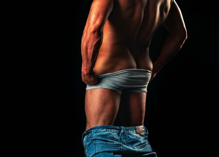 Guy. Muscular man, strong Athletic Man showing his perfect back isolated on black background