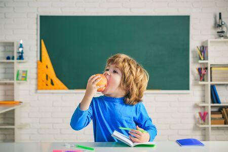 Friendly child eat apple in classroom near blackboard desk. Elementary school classroom. Kids Science education concept. Banque d'images - 141783903