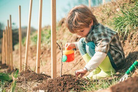 Little farmer with Shovel and watering can. Little helper in garden Planting flowers. Child Farmer planting in the vegetable garden Reklamní fotografie