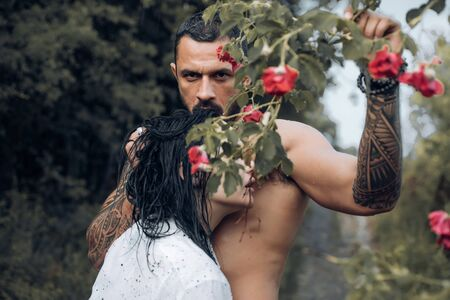 Sensual cople in love. Brutal bearded man holding rose ramification and embracing his beautiful woman. Eternal love and trust concept.