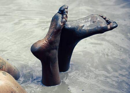 Dirty heels and feet. Legs butt in mud bath. Woman in the mud bath. Spa procedure and body care. Enjoying mud.