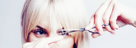 Blonde girl cut forelock. Close up hairstyle with bangs. Hair care concept.