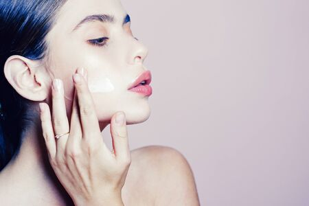 Skin cream concept. Facial care for female. Keep skin hydrated regularly moisturizing cream. Fresh healthy skin concept. Taking good care of her skin. Beautiful woman spreading cream on her face Stock fotó