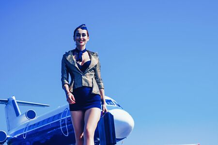 Transport tourism and air flights concept. Attendant. Commercial airplane flying with beautiful charming stewardess. Attractive flight attendant near airplane in airport. Copy spase, isolated on blue.