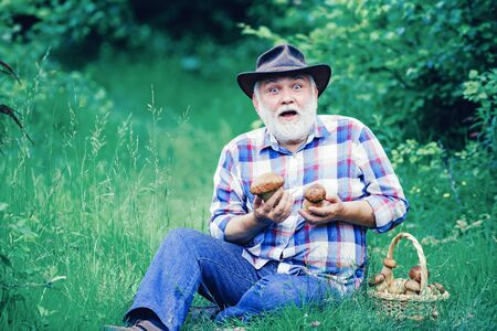 Grandfather with basket of mushrooms and a surprised facial expression. Mushrooming in forest, Grandfather hunting mushrooms over summer forest background. Foto de archivo
