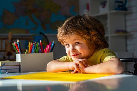Proceso educativo. Alumno lindo con trabajo escolar de cara divertida. Lindo niño preescolar con estudio de maestro en un aula.