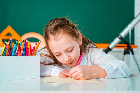 Close up portrait of cute child drawing with pencil. Chalkboard copy space. Banque d'images - 141935215