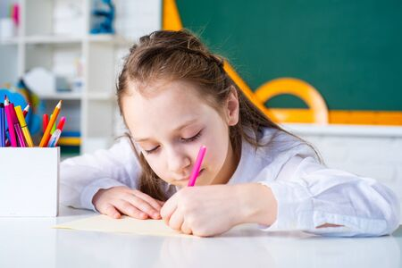 Kid is learning in class on background of blackboard. Preschool education. Home school for pupil. Banque d'images - 141935617