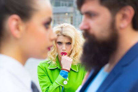 Obsessed ex girlfriend spying to a couple dating. She is obviously jealous. Bearded man cheating his girlfriend with another woman. Unhappy girl feeling jealous.