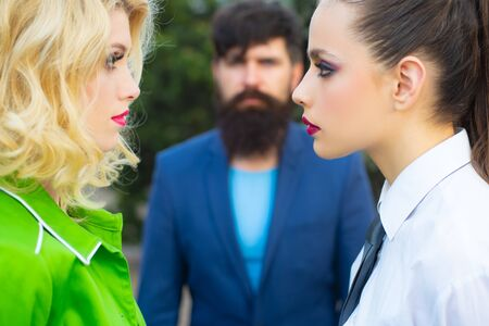 Infidelity and jealousy concept. Jealous man look at lesbian couple in love on street. Banco de Imagens