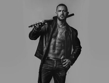 Brutal attractive bearded biker man with tattooed poses in black jacket. Copy space. Handsome bearded man. Serious stylish bearded man. Rock fan or gangster. Portrait of serious young man. Reklamní fotografie