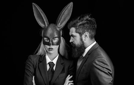 Funny bearded man and woman in carnival rabbit mask. Sweet lovely attractive adorable charming cheerful positive girl in bunny ears. Isolated black background.