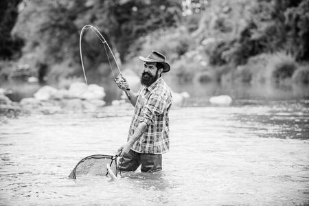 Bearded fisher in water. Young man fishing. Successful fly fishing. Fisher masculine hobby. Man with fishing rod and net. Master baiter. Fishing. Real happiness. Active sunny day.