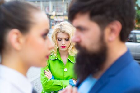 Divorce reason. Infidelity. Disloyal man walking with his girlfriend and looking amazed at another seductive girl. Obsessed ex girlfriend spying to a couple dating. Stock Photo