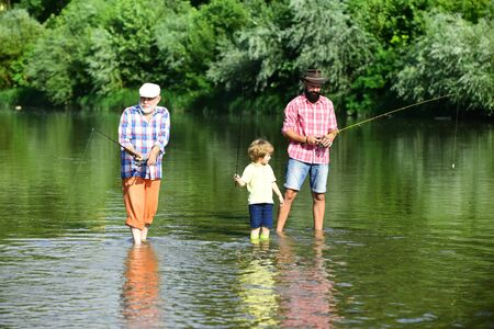 Family generation and people concept. Little boy on a lake with his father and grandfather.