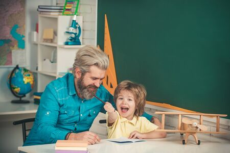 Father teaching son. Home study. Little boy pupil with happy face expression near desk with school supplies. Teacher and pupil in classroom. Elementary school classroom.