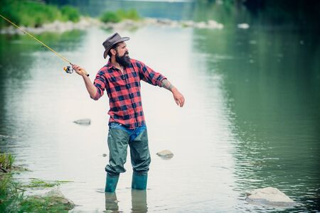 Bearded man catching fish. Summer leisure. Mature man fishing on the pond. Portrait of cheerful senior man fishing. Male fishing. Fishman crocheted spin into the river waiting big fish.