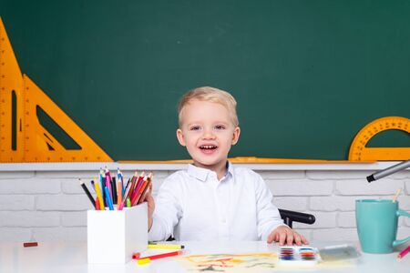 Cute pupil with funny face schooling work. Cute little preschool kid boy with teacher study in a classroom. Banque d'images - 142129707