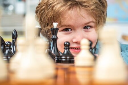 Little clever boy thinking about chess. Intelligent, smart kids. Games good for brain intelligence concept. Partrait close up, funny face.