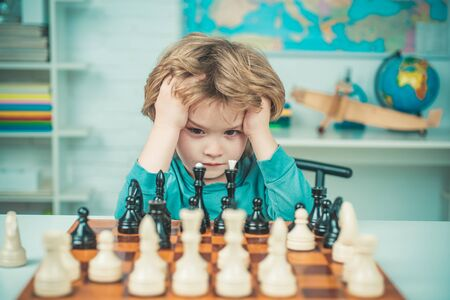 Clever concentrated and thinking child while playing chess. Thinking child. Chess, success and winning. Intelligent, smart ass kids. Games good for brain intelligence concept.