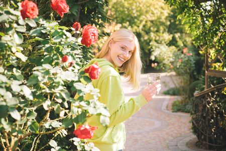 Happy young caucasian female wearing green long sleeve shirt holding a glass of water and smiling cheerfully, showing her preposition and inviting to be healthy. Body language. I like that. Be joyful.
