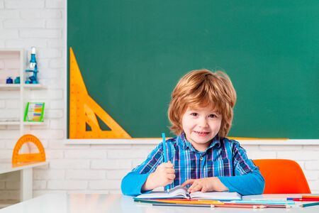 Portrait of Pupil of primary school study indoors. Pupil learning letters and numbers. Cute little preschool kid boy with teacher study in a classroom. Banque d'images - 142462565