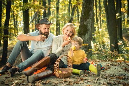 Family picnic at forest park. There is a basket with meal and toys for the kid. The concept of a happy family. Mom, dad and baby happy sitting at picnic blanket. Autumn season.