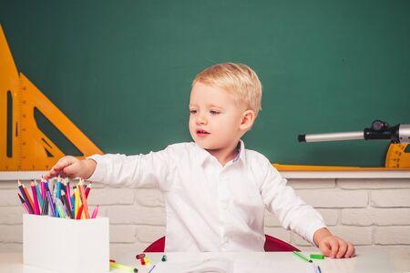 Kids from primary school. Happy school kids at lesson. Friendly child in classroom near blackboard desk.