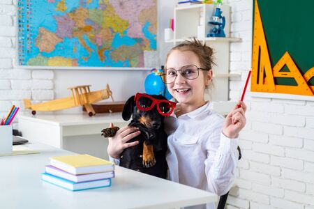 Pupil of primary school with funny dog against chalkboard. Nerd school girl with puppi in glasses smiling. Go back to elementary school Banque d'images - 142863032