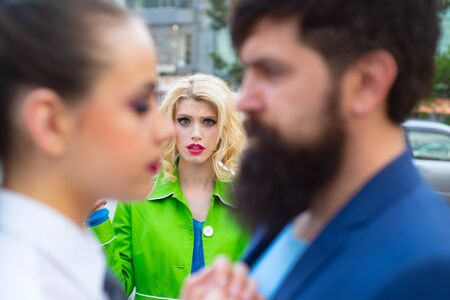 Cheating in marriage. Man looking other woman. Terribly jealous of them. Jealous woman look at couple in love on street. Unhappy girl feeling jealous. Banco de Imagens