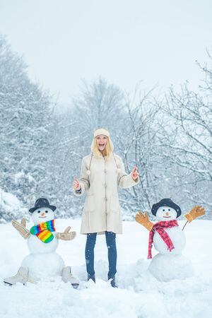 Beauty Winter woman with snowman in frosty winter Park. Girl in snow. Snowman and funny female model standing in winter hat and scarf with red nose.