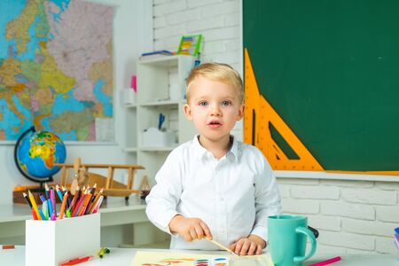 After school teaching. Elementary school and education. Happy cute industrious child is sitting at a desk indoors.