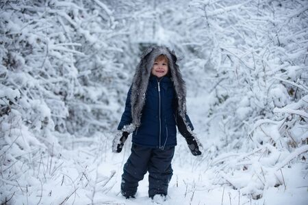 Children run on snowy field. Childhood on countryside. Kids in winter clothes. Cute little kid enjoying in the winter park in snow.