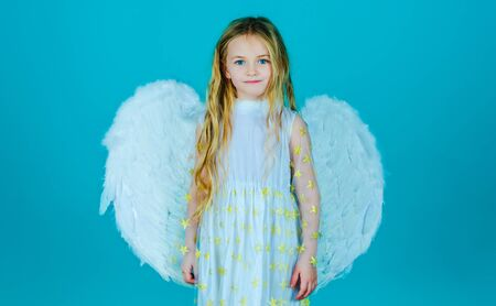 Cute child girl posing with angel wings. Beautiful little angel. Face of beautiful little angel girl on color background. Child angel with a beautiful wings.