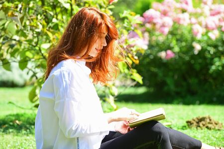 Student girl reading a book in park and sitting on grass. Redhead woman Sitting in grass with book in spring garden. Woman enjoying literature indoor in spring park. Imagens