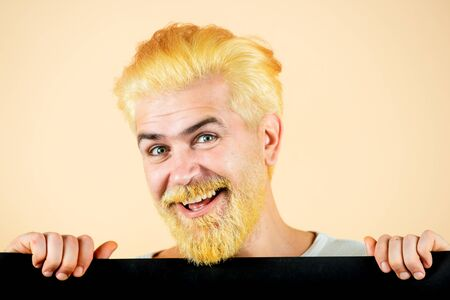 Happy man shows a sheet of paper in the camera on a color background. Male model holding yellow board.