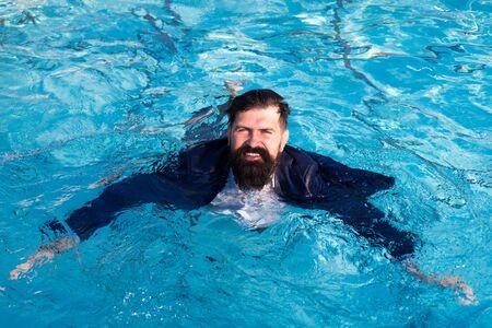 Homme d'affaires nageant en costume dans la piscine. Homme drôle et fou dans la piscine. Homme d'affaires s'amusant au bord de la piscine. Banque d'images