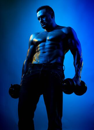Strong man with athletic body. Naked bodybuilder. Shirtless athletic man turned back on black background. 版權商用圖片