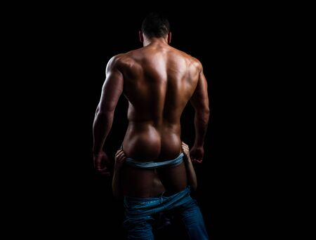 Bare torso. A man in underpants on black background isolated. Mens ass in underwear. Naked male ass. Oral sex. Woman with the tongue of the male buttocks. 版權商用圖片