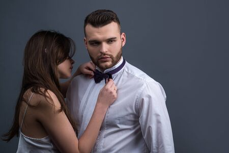 Portrait of elegant couple posing together on grey studio background. Elegant modern male accessory. Women holding bowtie ready to dress it on man in white shirt. Couple getting ready for event. Foto de archivo