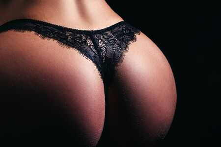 Perfect female body in shape with sexy back and big Butt. Black lingerie. Beautiful butt ass in elegant black panties. Sexy butt, black panties. Woman in lingerie close up. Womans buttocks in bikini.