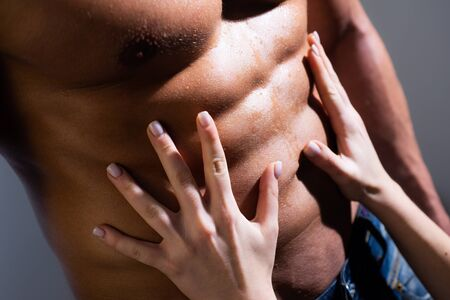 Woman hands embracing sexy man six pack abs. Close up of muscle man torso. Passionate couple. Hot brunette woman and handsome muscular man in bedroom.